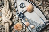 Frame decorated by shells and ropes lying on stones at shore — Stock Photo