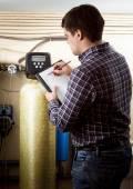 Engineer writing down meter reading on industrial counters — ストック写真