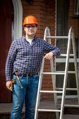 Carpenter in hard hat posing at metal step ladder — Stock Photo