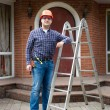 Manual worker posing with metal ladder against big house — Stock Photo #71719575