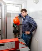 Confused plumber looking at complicated heating system — Stock Photo