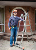 Manual worker posing with metal ladder against big house — Stock Photo