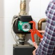 Closeup of plumber repairing heating system with red pliers — Stock Photo #71723401