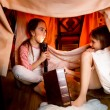 Sisters telling scary stories under blanket at night — Stockfoto #72280469