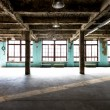 Abandoned warehouse at factory with long hallway and big windows — Stock Photo #72280999