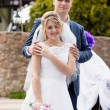 Young groom hugging cute bride around shoulders — Stock Photo #72283407