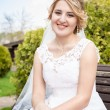 Portrait of happy smiling bride sitting on bench at park — Stock Photo #72283661