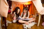 Girls reading book with flashlight at house made of blankets — Stock Photo