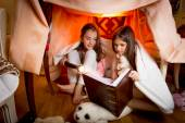 Two sisters sitting in house made of blankets and reading book — Stock Photo