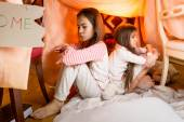 Two resentful sisters sitting on floor at bedroom back to back — Stock Photo