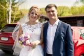 Portrait of smiling bride and groom posing at sunny day at park — Stock Photo