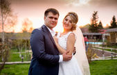 Portrait of happy bride and groom hugging at sunset in park — Stock Photo