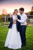 Groom putting jacket on brides shoulder at sunset in park — Stock Photo