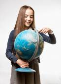 Smiling girl in school uniform pointing at Earth globe — Stock Photo