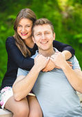 Happy hugging couple posing at summer park — Stock Photo