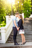 Romantic couple in love posing on stairs at park at sunny day — Stock Photo