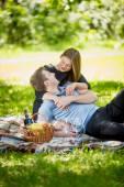Portrait of cute woman hugging boyfriend on blanket at picnic — Foto de Stock