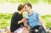 Romántica pareja besándose y bebiendo vino en picnic — Foto de Stock