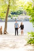 Couple in love holding hands under big tree at riverbank — Stock Photo