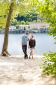 Couple in love posing under tree at riverbank at sunny day — Stock Photo