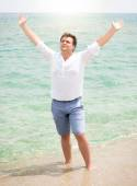 Handsome man in shirt enjoying sea and raising hands in the sky — Stock Photo