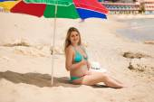 Pregnant woman awaiting baby relaxing on beach under parasol — Stock Photo