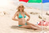 Pregnant woman relaxing and on beach and pointing at stomach — Stock Photo