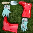 Garden gloves, spade and red rubber boots lying on green grass — Stock Photo #75943871