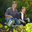 Smiling man and cute girl working at garden with watering can — Stock Photo #75944777