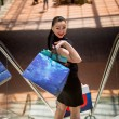 Elegant woman with shopping bags standing on escalator at mall — Stock Photo #75945991
