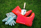 Closeup of gloves, gumboots and shovel on green grass — Stock Photo