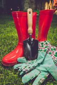 Toned filter of garden tools and red boots on meadow — Stock Photo