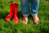 Barefoot girl standing next red garden gumboots on grass — Stock Photo