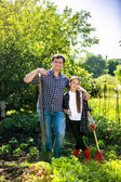 Man and daughter spudding lettuce garden bed at hot summer day — Stock Photo
