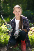 Cute smiling girl in gloves and gumboots posing at garden — Stock Photo