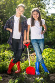Two girls in gumboots posing with shovel on garden bed — Stock Photo