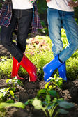 Two girls in gumboots posing on garden bed at hot summer day — Stock Photo