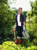 Smiling girl working at garden with shovel and watering can — Stock Photo