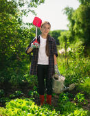 Smiling girl posing at garden with spade and watering can — Stock Photo