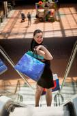 Elegant woman with shopping bags standing on escalator at mall — Stock Photo