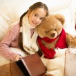 Cute smiling girl reading book with teddy bear in bed — Stock Photo #76614335