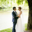 Bride with long hugging with groom under big tree at park — Stock Photo #76616357