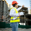Engineer in hardhat and safety jacket checking building site — Stock Photo #76616653