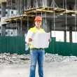Architect at work reading blueprints on building site — Stock Photo #76616727