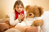 Girl playing and measuring teddy's bear temperature with thermom — Stock Photo