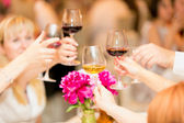 Closeup of hands clinking glasses with red and white wine — Stock Photo