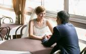 Smiling bride and groom sitting at cafe and holding hands — Stock Photo