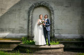 Bride and groom posing at park under floral arch — Stock Photo