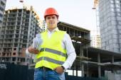 Site manager posing with blueprints against unfinished building — Stock Photo