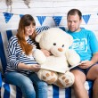 Pregnant woman and husband reading big book to teddy bear on sof — Stock Photo #78588644